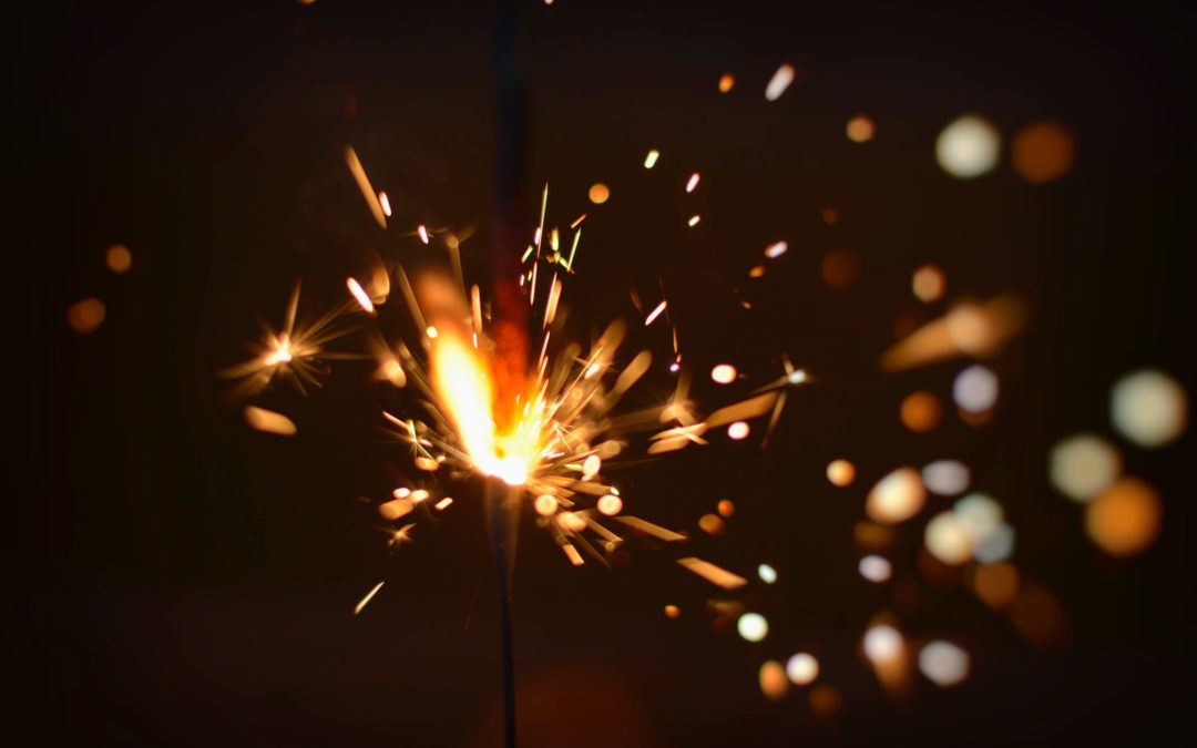 Image of a sparkler alight mid way through burning against a black background